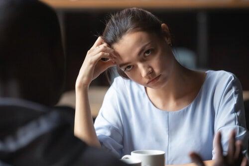 Mujer aburrida hablando con un amigo pensando en cómo corregir a una persona que mantiene una idea equivocada