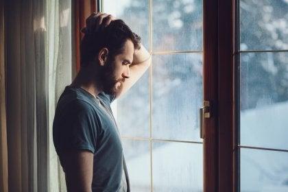 Hombre triste cerca de la ventana pensando en las heridas que deja la infidelidad
