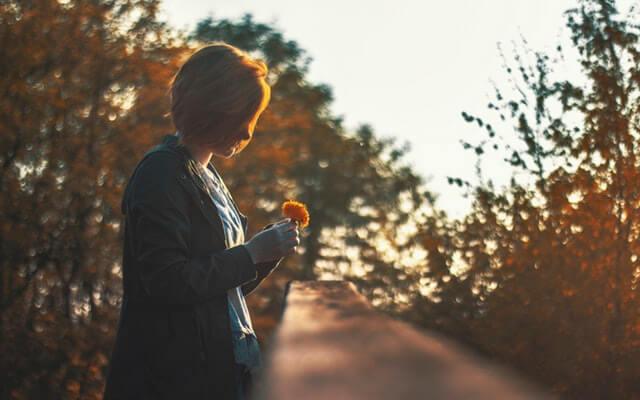Mujer mirando una flor
