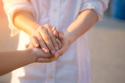 Persona agarrando las manos a otra