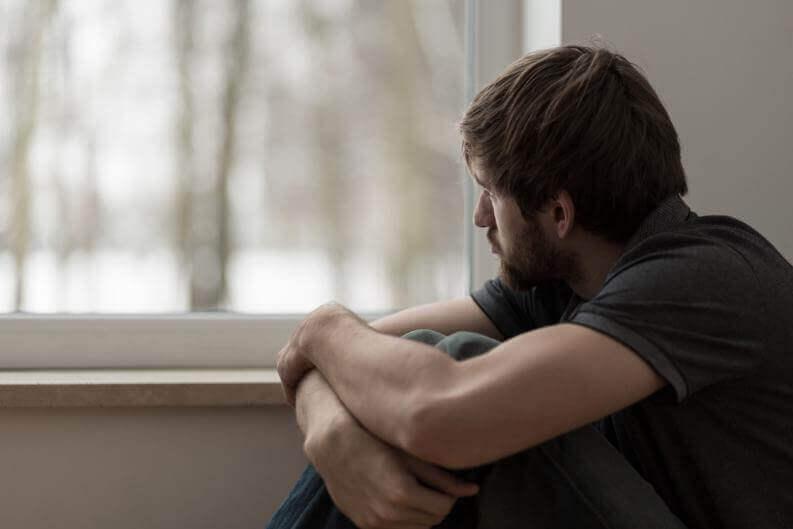 Chico mirando por la ventana con pensamientos negativos durante el COVID-19