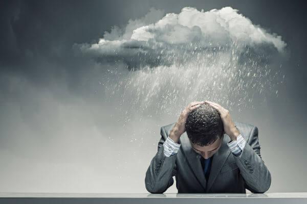 Hombre con nube y lluvia pensando que a mal tiempo, buena cara