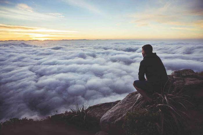 Hombre en la montaña pensando en la esperanza y perseverancia