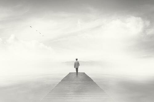 Hombre caminando por un puente con niebla representando cómo saber reaccionar