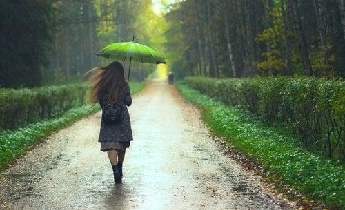 Mujer paseando con paraguas pensando que «podría ser peor»