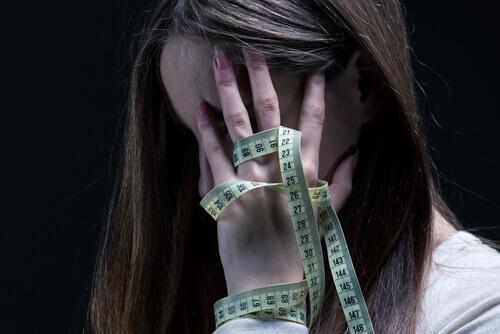 Mujer con anorexia con el metro en la mano