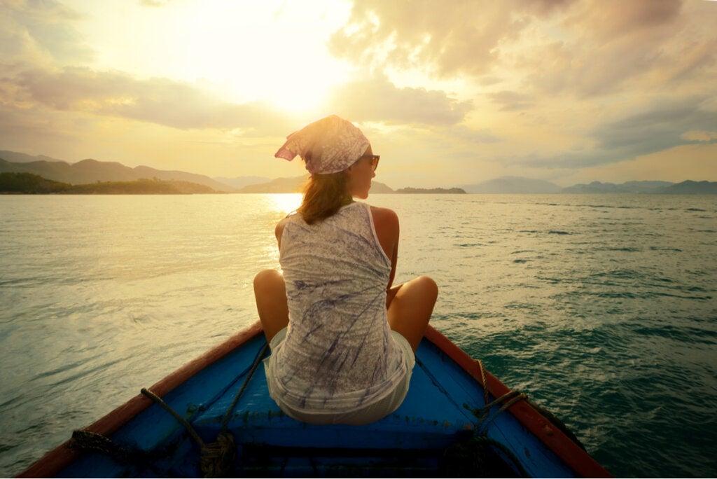 Mujer en una barca al atardecer dejando de Rumiar pensamientos