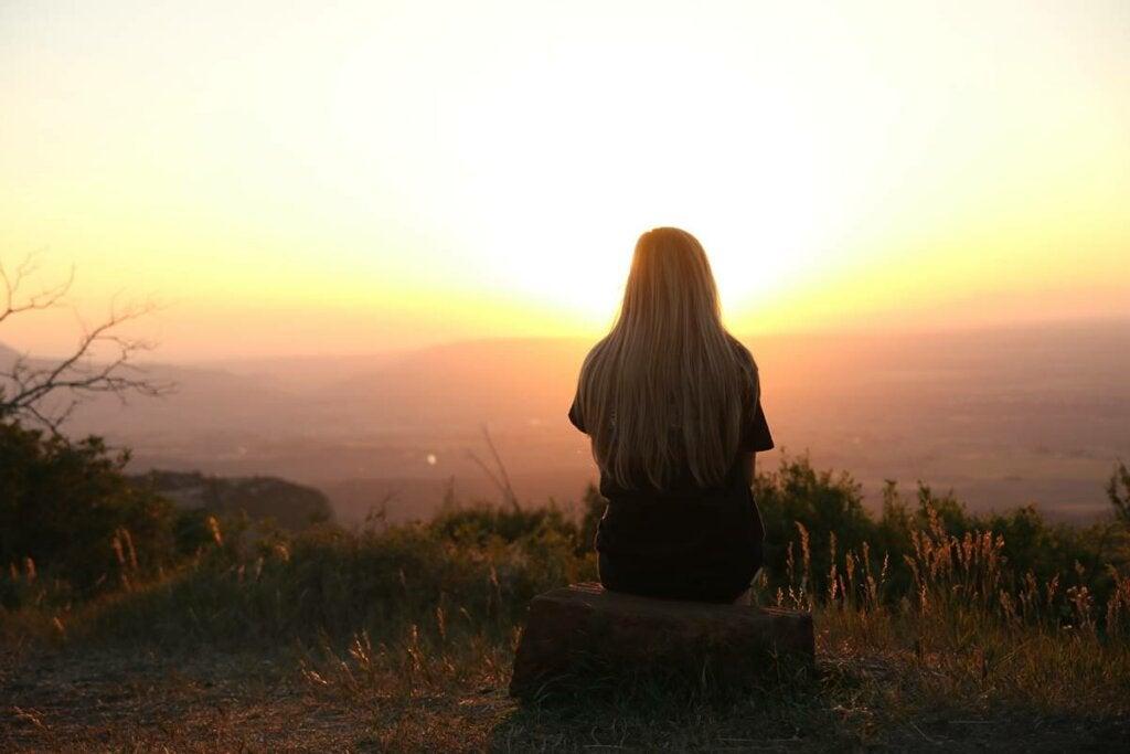 Chica ante el amanecer pensando en dejar atrás el pasado