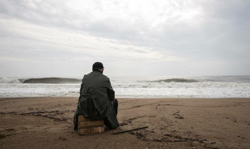 Hombre sentado mirando el mar
