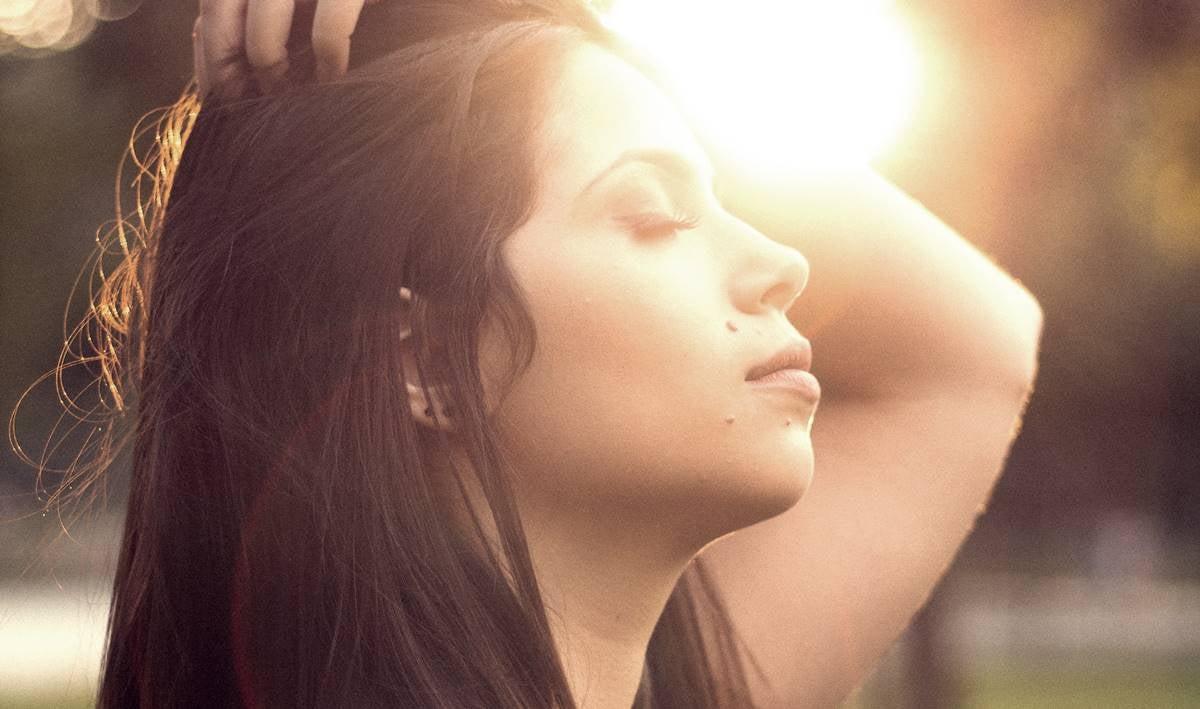 Chica con los ojos cerrados ante el sol preguntándose ¿Por qué suspiramos?