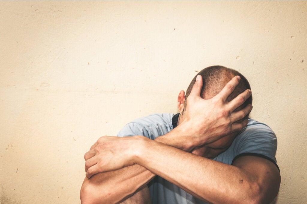 Hombre triste sentado en el suelo debido a la ansiedad crónica