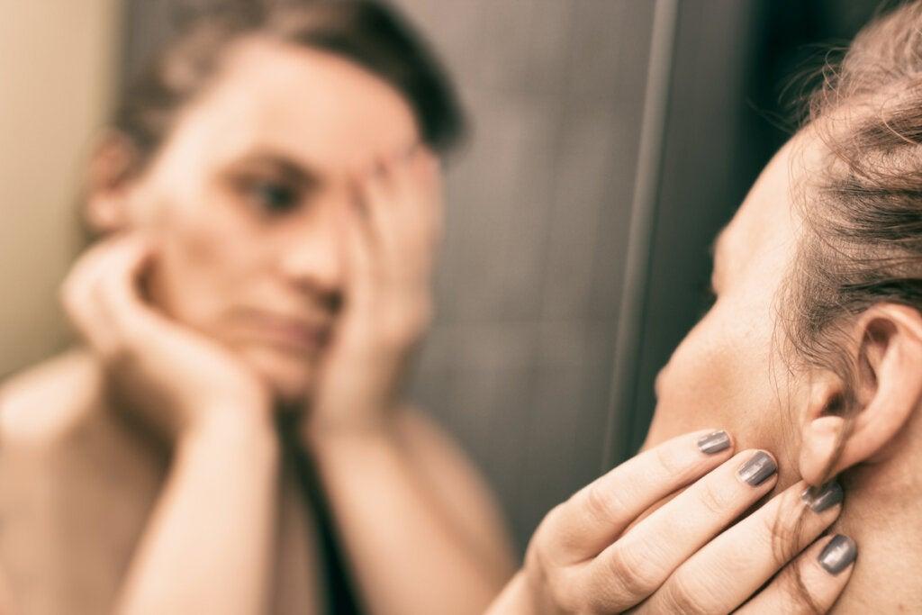 Mujer triste mirándose al espejo debido a una alteración de la noradrenalina