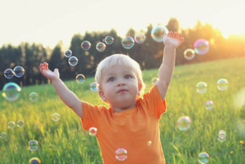 Niño jugando pompas de jabón que necesita la administración de la hormona del crecimiento