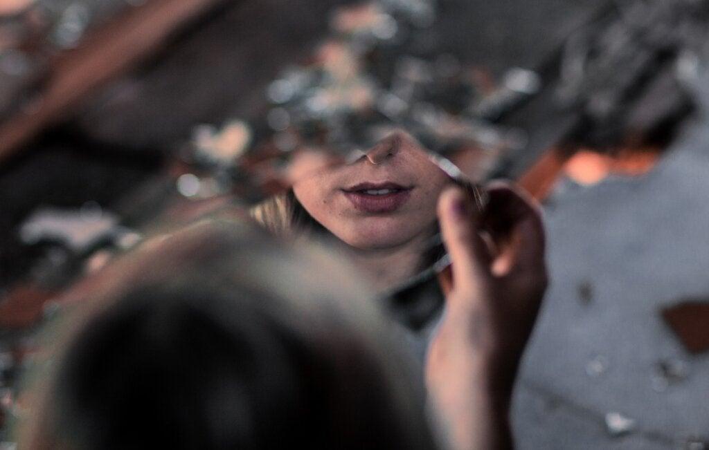 Mujer ante cristal que sufre el síndrome de Orfeo