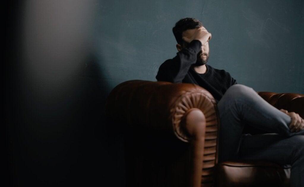 Hombre sentado en sofá que sufre vértigos psicógenos
