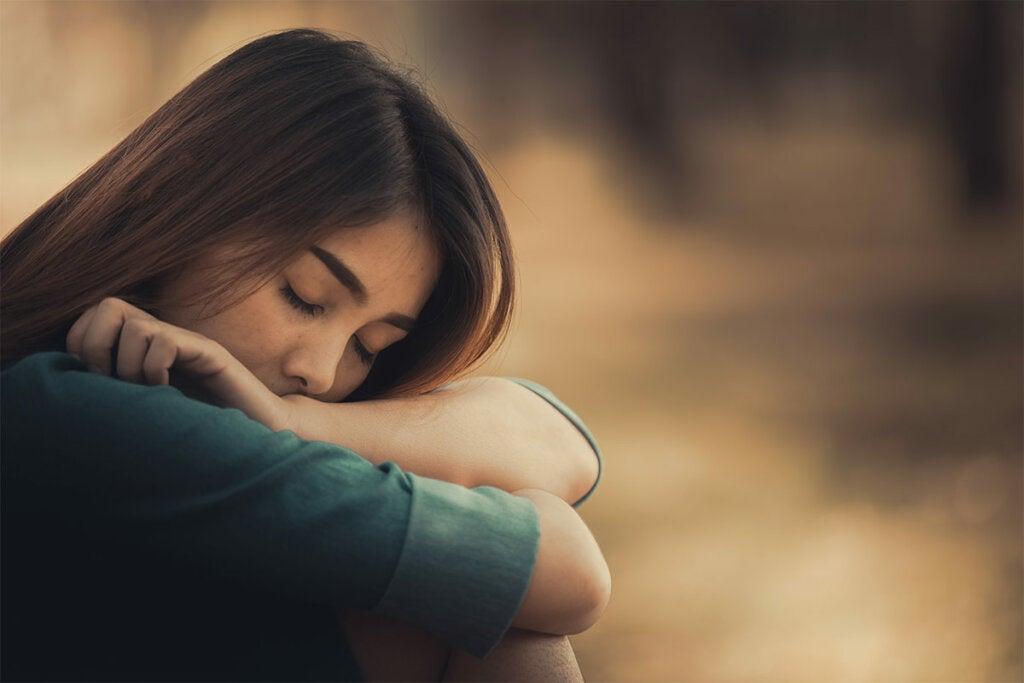Mujer triste sentada pensando en ¿Cómo afecta una infancia difícil a las relaciones adultas?