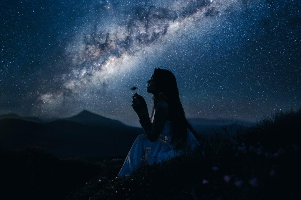 Niña en el campo por la noche sintiendo la fascinación
