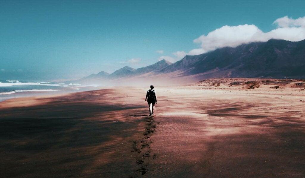 Mujer caminando por escenario desolado