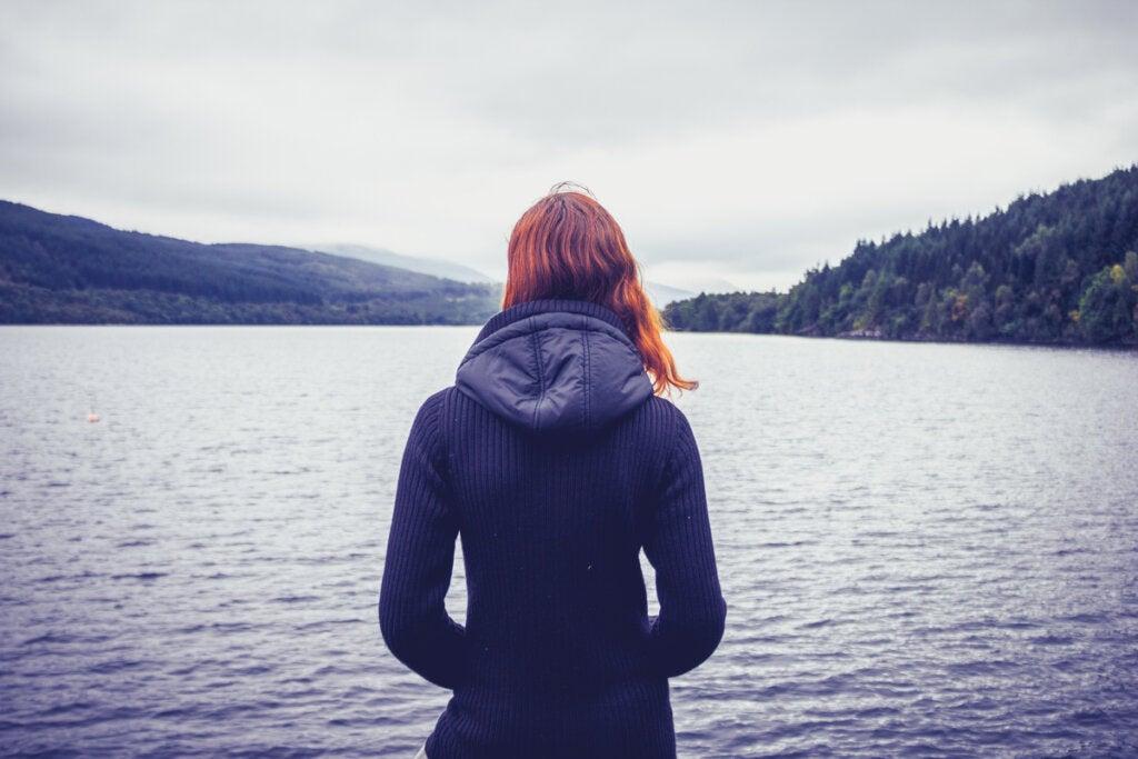 Mujer sola en el lago pensando representando las frases sabias para pensar sobre la vida