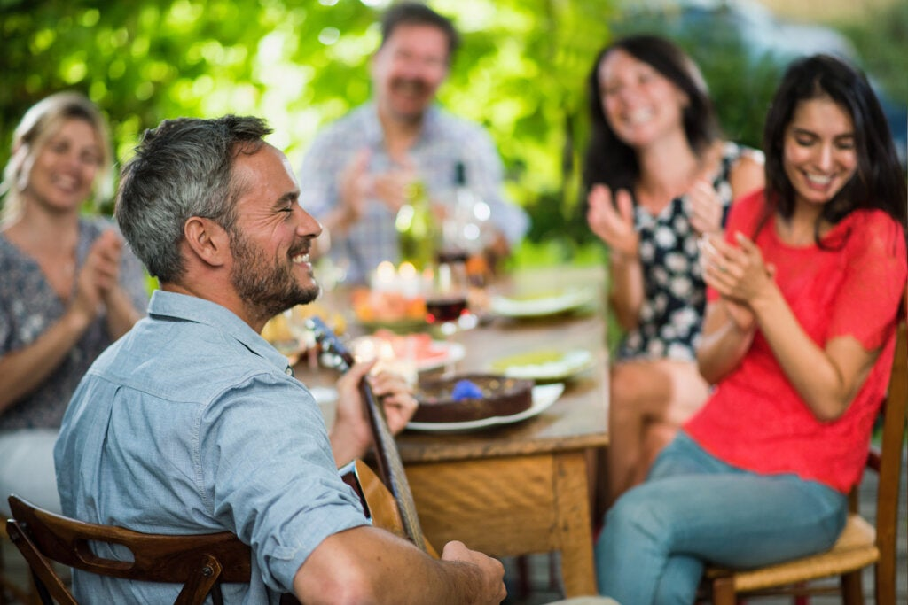Hombre tocando una guitarra en una comida de amigos