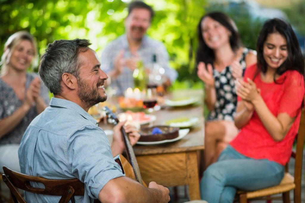 Hombre tocando una guitarra en una comida de amigos representando a las Personas emocionalmente intensas y sensibles