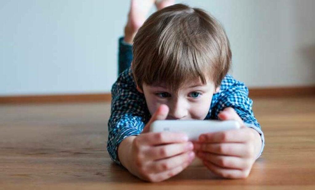 pequeño con móvil simbolizando cómo las pantallas aceleran a los niños y empeoran su humor
