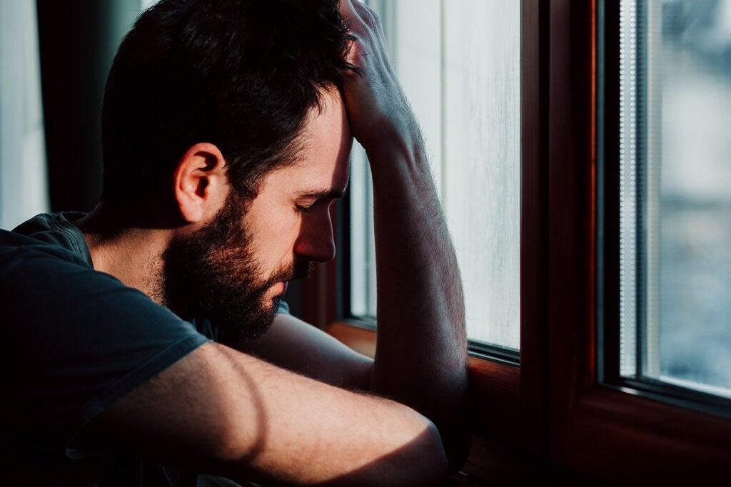 hombre apoyado en ventana preguntándose qué hacer cuando me siento muy nervioso