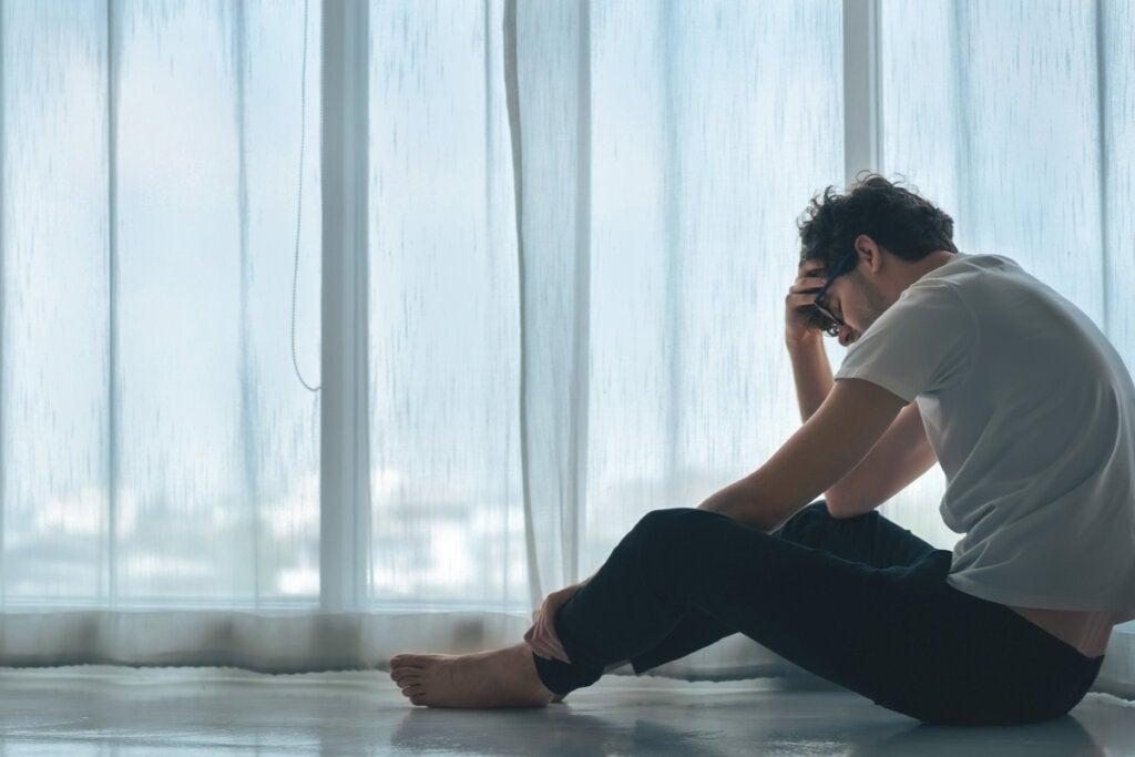 Hombre llorando sentado en el suelo