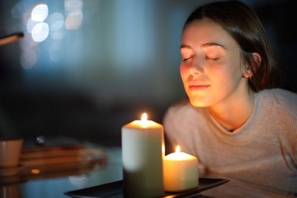 Mujer con dos velas haciendo un ritual para soltar el pasado