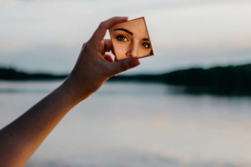 Mujer mirando el reflejo en el espejo