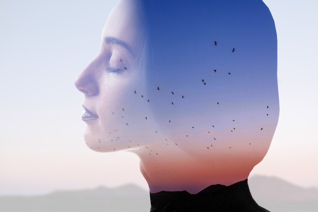 Mujer pensando con pájaros en la mente trabajando su autoconciencia emocional