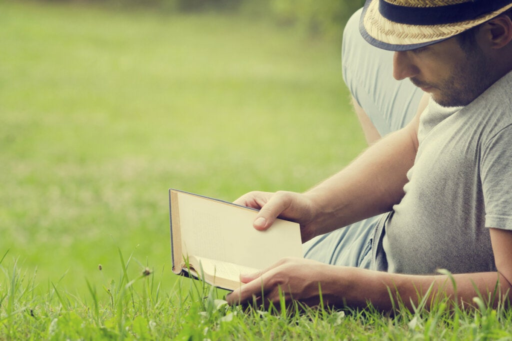 Hombre leyendo un libro en el césped