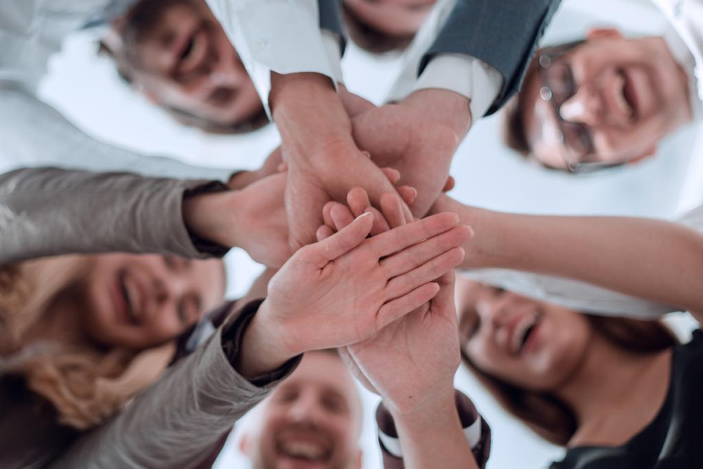 Personas uniendo sus manos