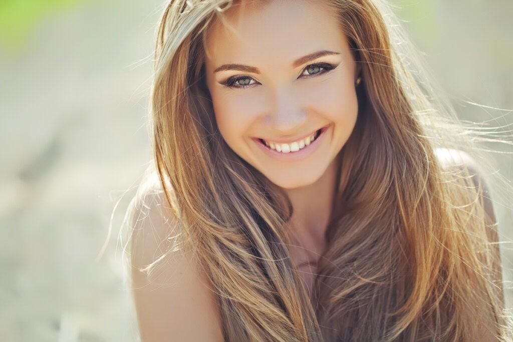Mujer guapa sonriendo aplicando el secreto para causar una mejor impresión