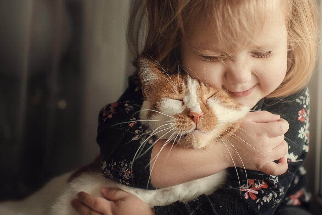 Niña abrazando a un gatito