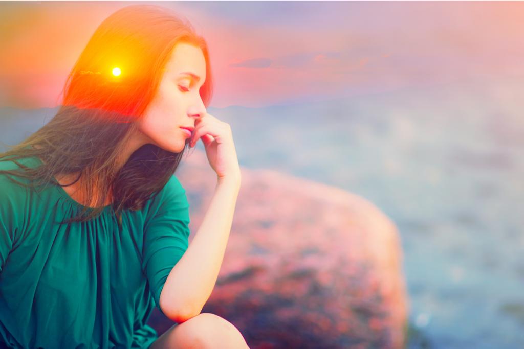Mujer con una luz en la mente y los ojos cerrado representando la emoción mudita