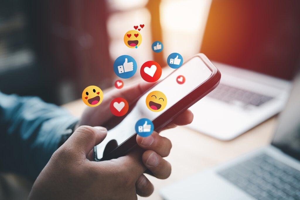 Persona utilizando emoticonos en el móvil